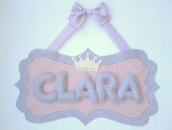 Encantador enfeite para porta de maternidade com coroa de princesa, nome do bebê em feltro e laço de tecido. Possui aplicação de pequenos brilhinhos na coroa.  Dimensões: 36cm de altura (do laço ao fim do panô), 44cm de comprimento e 3cm de largura. R$ 162,90