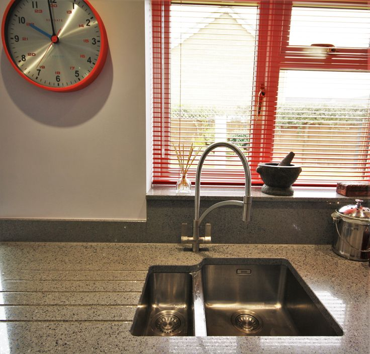Stainless Steel, one and a half bowl sink. Under-mounted, with drainer grooves to the left hand side of the worktop.