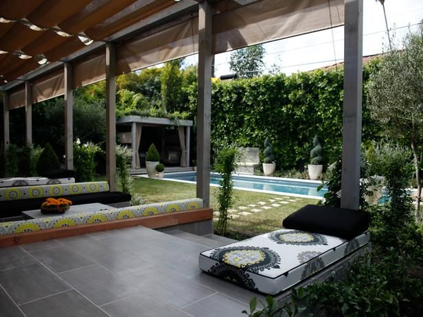 Curtains made from durable outdoor fabric hang along the side of the pergola to allow homeowners Anne Heche and James Tupper control the amount of sun entering the space, as seen on The Outdoor Room by Jamie Durie on HGTV.