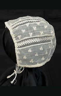 Hand-embroidered infant's bonnet, c.1800. Made from sheer cotton muslin with insets of needle-run tulle. The embroidered florets are executed in chain stitch—they appear raised above the surface. The bonnet has drawstring ties on the lower edge and along the front. The purity and restraint of textured white stitches on a sheer white ground perfectly suited the Neoclassical aesthetic.
