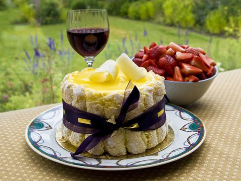 Pictured is a Lemon charlotte cake with glass of wine and a bowl of strawberries set on a table overlooking the garden. This is a beautiful cake perfect for any tea, dinner party or garden party. This particular cake is a cold cake and sometimes called a Charlotte Russe.