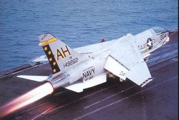 An F-8 Crusader takes off from a carrier with its afterburner on.