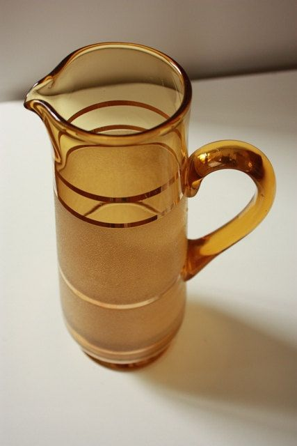Australian buyers, please check postage rates for your State under shipping. The listed rate of $8.65 is for Sydney. I will reserve and adjust postage prior to purchasing. Lovely Tall Art Deco textured Amber Coloured Glass Jug with gold coloured rings. This jug has come from a Family Estate In Leura, Blue Mountains. Measures 30cm Tall x 8cm rim Condition: Very good used condition with no chips or cracks. The is a slight pale run mark to the exterior glass.    Shipping: I am happy to combine…