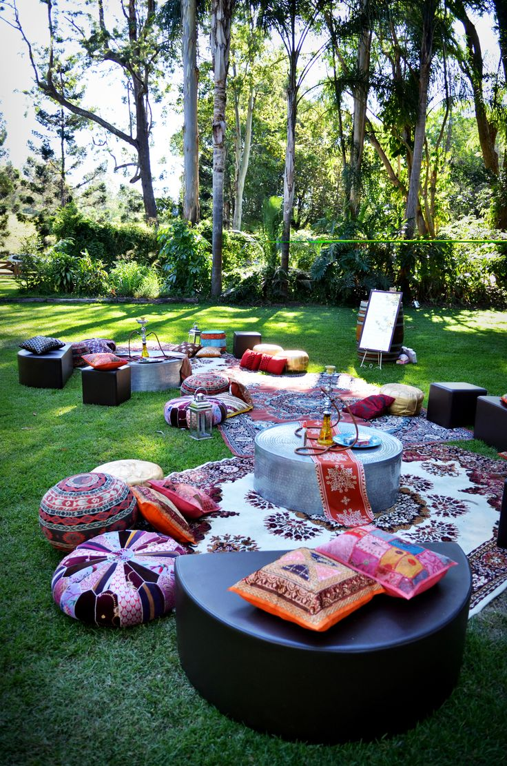 Cocktail lounge on lawn with pouf, scattered cushions and shisha hooka
