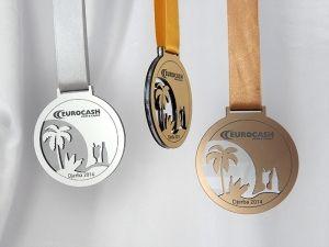 Medal pamiątka związany z wakacjami przedstawia wyciętą palmę obok niej znajdują się napoje. Wykonany z pleksi bezbarwnej i laminatu w trzech kolorach – złotym, srebrnym i brązowym.