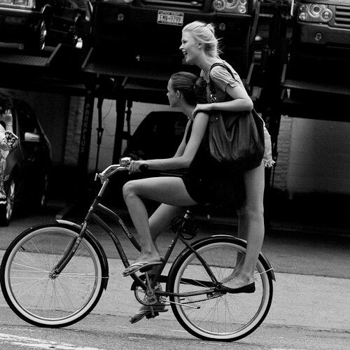 Black & white - two girls riding a bicycle, smiling!