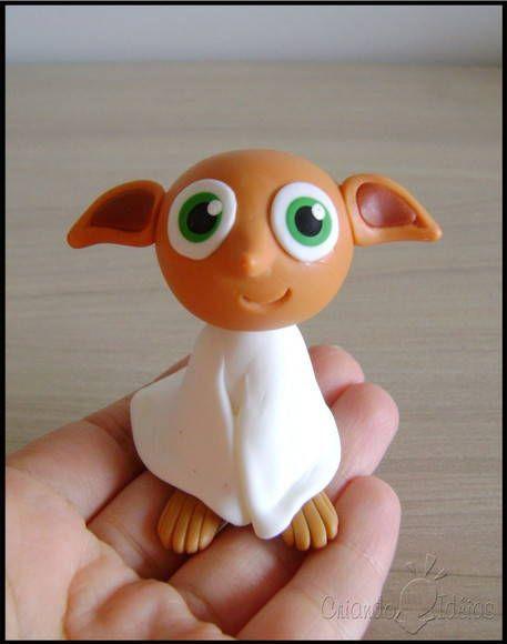 """O elfo doméstico Dobby em versão chibi. (estilo infantil simplificado), ideal para presentear! """"Personagem"""" da saga literária Harry Potter, da escritora britânica J.K. Rowling.  Ele vai sobe base de acrílico!  OBS: O prazo de produção está sujeito a alteração, de acordo com a nossa agenda de pedidos no momento.  Material utilizado: porcelana fria (biscuit).  ----------- Novidade! ----------- Tenho também vários outros personagens do livro neste mesmo estilo chibi! Você pode conferí-los na…"""