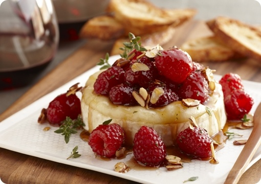 Warm Brie w/Honeyed Raspberries & Almonds  1/2 cup (2 oz) sliced almonds  1 wheel (13.3 ounces) ripe Brie, top rind sliced off, chilled  1/4 cups honey  1 tsp balsamic vinegar  1/2 tsp finely chopped fresh thyme  1 pkg (6 oz) Raspberries  Water crackers or baguette slices for serving
