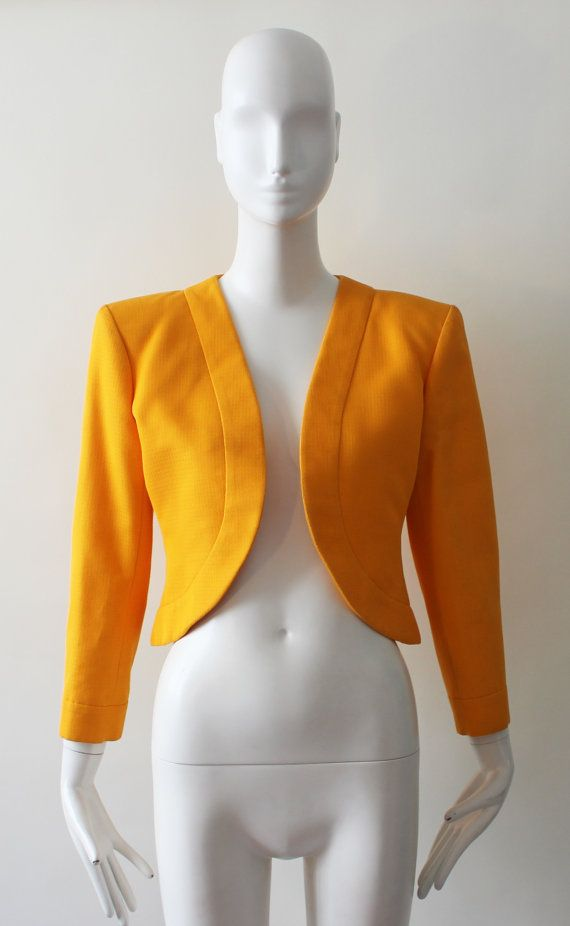 Add a pop of color to any outfit with this vintage Yves Saint Laurent school bus yellow bolero jacket. It features beautiful yellow gem buttons