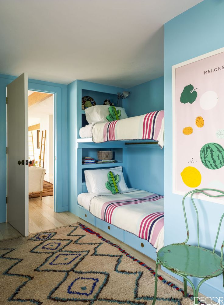 In a child's bedroom, the bunk beds sport throws from Pottery Barn Kids and Cactus pillows from the Land of Nod, the walls are painted in Benjamin Moore's Fairy Tale Blue, and the antique Azilal rug is Moroccan.
