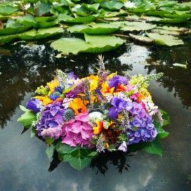 Drijvend bloemstuk op een vijver.