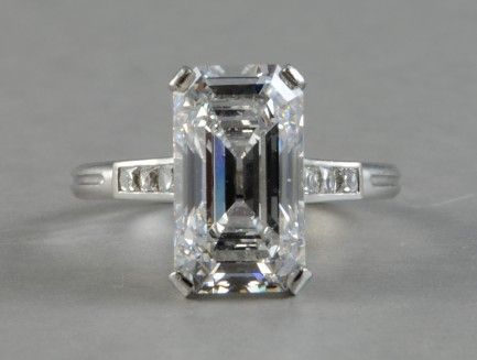 """This exquisite ring is a rare and exceptional piece from Tiffany & Co circa 1920′s. The ring is crafted in platinum and features a 3.95 carat emerald cut center diamond of """"D"""" color and """"SI1″ clarity. The stunning center diamond is accented by 3 French cut diamonds on each side. There is no better representation of Art Deco era jewelry design than this incredible vintage ring from Tiffany & Co."""