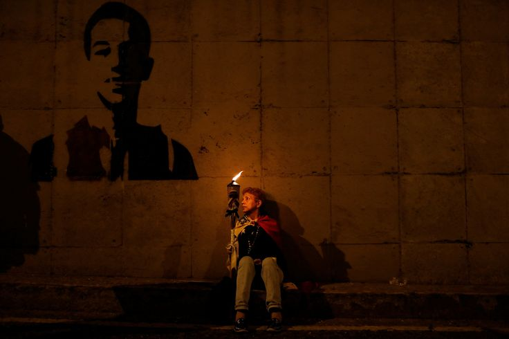 Caracas, Venezuela: A woman holds a torch while sitting next to graffiti of 17-year-old protester Neomar Lander, the latest fatality from the anti-government unrest.  Photograph: Carlos Garcia Rawlins/Reuters