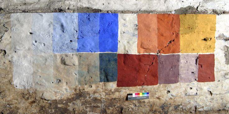 Proefvlakjes van verschillende kleuren kalkverf op een oude muur. Bovenste rij v.l.n.r.: kalkverf zonder pigment, 4x gekleurd met ultramarijn in verschillende verhoudingen, niet geschilderd, 2x rode oker, 2x ijzeroxide geel. Onderste rij v.l.n.r.: kalkverf helder gemaakt met een beetje recket blauw, 4x Berlijns blau, ijzeroxide rood, Engels rood, 2x paarse dodekop en rode dodekop. Het Berlijns blauw is verkleurd door de inwerking van de kalk en dus niet geschikt voor dit type verf.