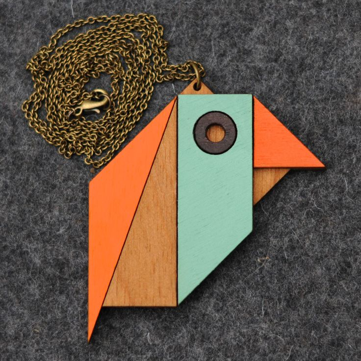 Look at these shapes and tell me what you see. A hat? A brooch? Or a pterodactyl?  No. The correct answer was robin.  This robin necklace is inspired by the classic tangram puzzle. It was created using quality wood, hand-painted with a retro colour palette.  H 6.5cm X W 8cm X D 0.7cm
