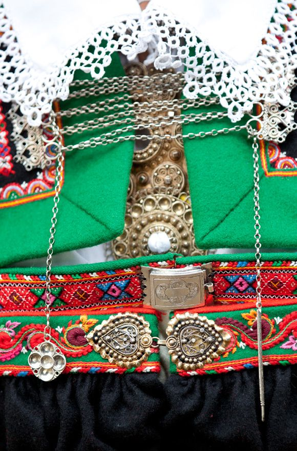 This Setesdal bunad layers two wool dresses with braid trim, topped by silver pins, buckles, hooks and lacing. A bridal bunad adds a third wool dress in red.