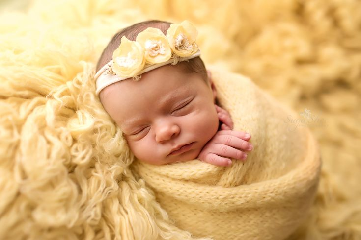 Newborn pose baby girl wrapped in yellow net wrap wearing yellow floral headband laying on a yellow flokati