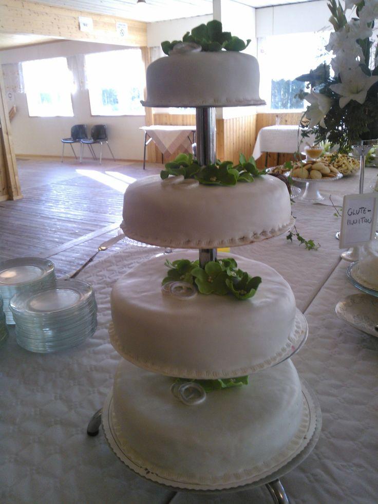 Vadelmatäytteinen kerroskakku, koristeena hopeiset sormukset ja vihreät kukat.