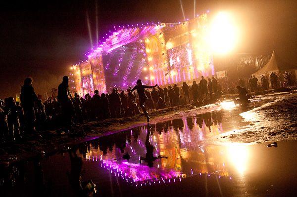 """Publiczność pod woodstockową sceną wygląda niezwykle w odbijających się wodzie kolorowych światłach. To zdjęcie zrobiono podczas jubileuszowego koncertu """"40 lat amerykańskiego Woodstocku""""."""