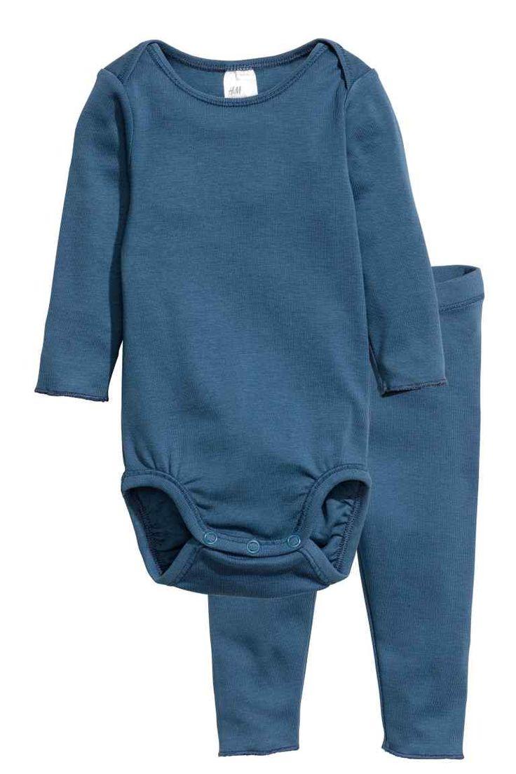 Romper en legging: BABY EXCLUSIVE/CONSCIOUS. Een set van zacht ribtricot van biologisch katoen bestaande uit een romper met lange mouwen en een legging met elastiek in de taille. De romper heeft een overslag op de schouders en een drukknoopsluiting in het kruis. De set is onder aan de mouwen en de pijpen afgewerkt met een overlocksteek.