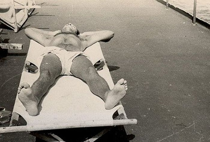 Hairy-chested sailor sunbathing on deck - World War II