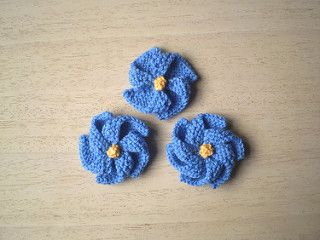 These are simple garter stitch flowers, knitted in one piece, which can be used as brooches or decorations. A pattern for stalks and leaves is also included, should you want to knit a bouquet.