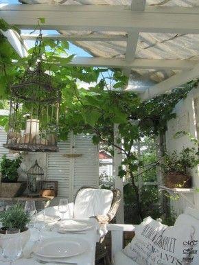 Een brocante tuin? Tuurlijk kan dat: mooie oude luiken, kroonluchtertje, vogelkooitjes zinken accessoires en mooie linnen kussen: allemaal verkrijgbaar bij Old BASICS