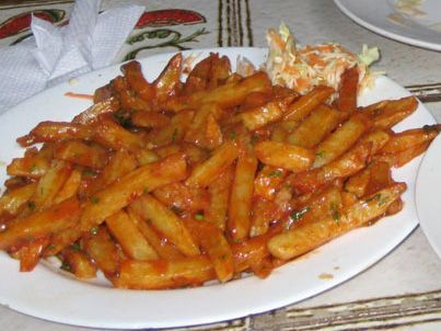Masala Chips Recipe Ingredients: 1kg bag oven Fries 2 large onions or 3 medium onions, sliced long 1 can of crushed tomatoes (or 5-6 large fresh tomatoes, crushed) 10-15 medium sized cloves of garlic 2-3 heaped tbsp chilli powder 1-2 tsp salt 5-6 tbsp tomato ketchup Coriander, chopped