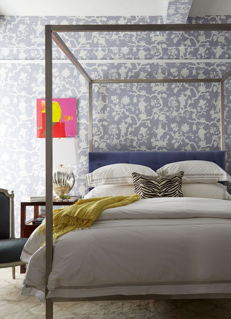 A contemporary four-poster in the guest room sets off the fanciful patterns of Schumacher's Shantung Silhouette wallpaperand the subtle gradations of the rug.