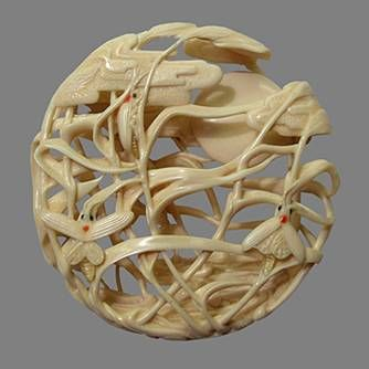 """Moon, reeds and fireflies"""" was carved from ivory mammoth tusk, inlays were done from black water buffalo horn and red apple coral, the glows were done from golden amber. Its size is 2 inches across and ½ inch thick. The loop for the cord was done opposite himotoshi. 2007"""
