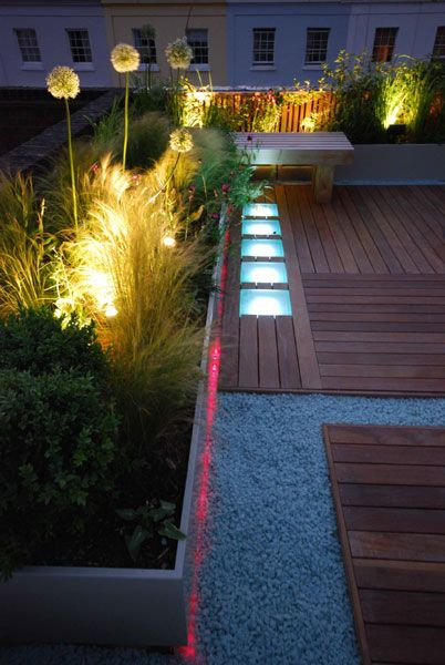 Frosted glass panels were inset into the decking which are under lit at night creating a magical dramatic effect and frosted glass chippings which are also lit run between the stretches of timber decking.
