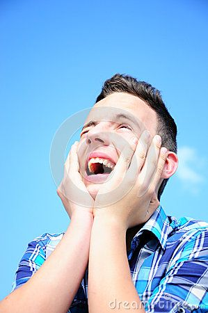 Teenage boy excited, looking upwards holding his hands around face