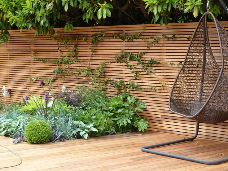 Modern Horizontal Plywood Fence For Backyard Design Feature Beautiful Natural Plants And Brown Wicker Swing Chair Also Laminated Wooden Flooring