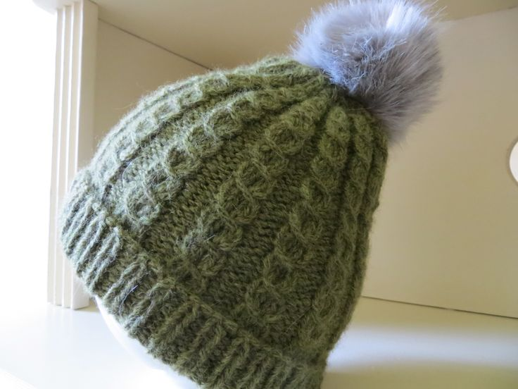 handgestrickte Mütze, gestrickt im falschen Zopfmuster mit Kunstfellbommel, Merinowolle
