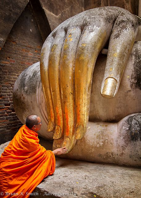 Sukhothai Monk venerates the gold-leaf covered hand of the Phra Achana Buddha inside a mondop (altar pavilion) at Wat Si Chum (Temple Of The Bodhi Tree).