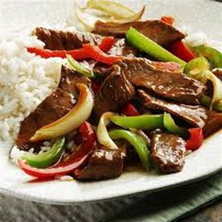 Slow Cooker Pepper Steak: 2 pounds beef sirloin, cut into 2 inch strips , garlic powder to taste , 3 tablespoons vegetable oil , 1 cube beef bouillon , 1/4 cup hot water , 1 tablespoon cornstarch , 1/2 cup chopped onion , 2 large green bell peppers , 1 (14.5 ounce) can stewed tomatoes , 3 tablespoons soy sauce , 1 teaspoon white sugar , 1 teaspoon salt