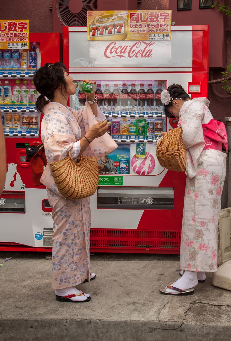 Tradition vs modernity - Two female tourists dressed in japanese traditional yukata refresh themselves with drinks from a vending machine.