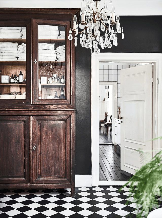 Antique bathroom storage and a black white floor in a stunning industrial-style home in Lund, Sweden. Credits: Emma Persson Lagerberg / Andrea Papini. Elle Decoration.