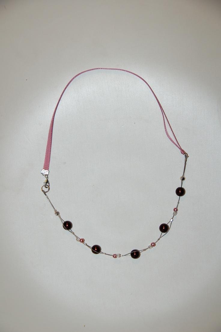 Collana fatta a metá con nastro di grosgrain rosa antico e metá un doppio filo di acciaio con perle grandi marroni, piccole rosa e mezzi cristalli trasparenti. Chiusura laterale con moschettone.