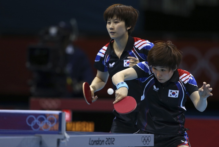 South Korea's Dang Ye-seo, right, returns a shot in front of partner Seok Ha-jung in a doubles match against Singapore during the women's team table tennis bronze medal matchs at the 2012 Summer Olympics, Tuesday, Aug. 7, 2012, in London.