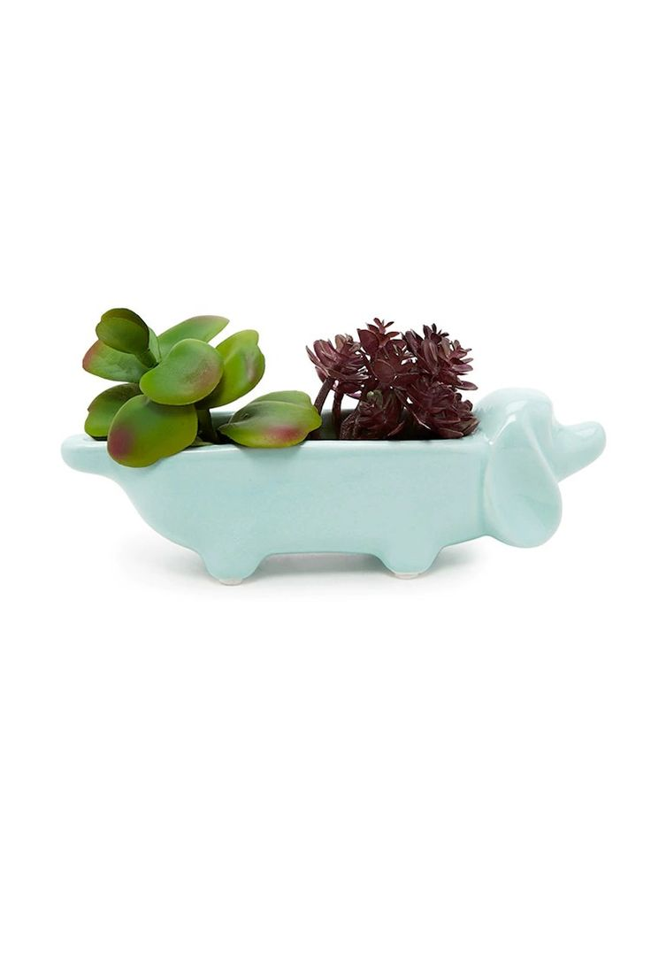 A decorative ceramic planter featuring a dachshund dog design and faux plants.