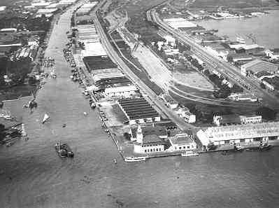 Luchtopname van de Tandjoeng Perak handelshaven van Soerabaja met het havenkantoor met uitkijktoren en de Kali Mas rivier, datering vóór de oorlog. Links de marinehaven Oedjoeng en rechts het Soerabaja Droogdok (Indisch Herinneringscentrum)