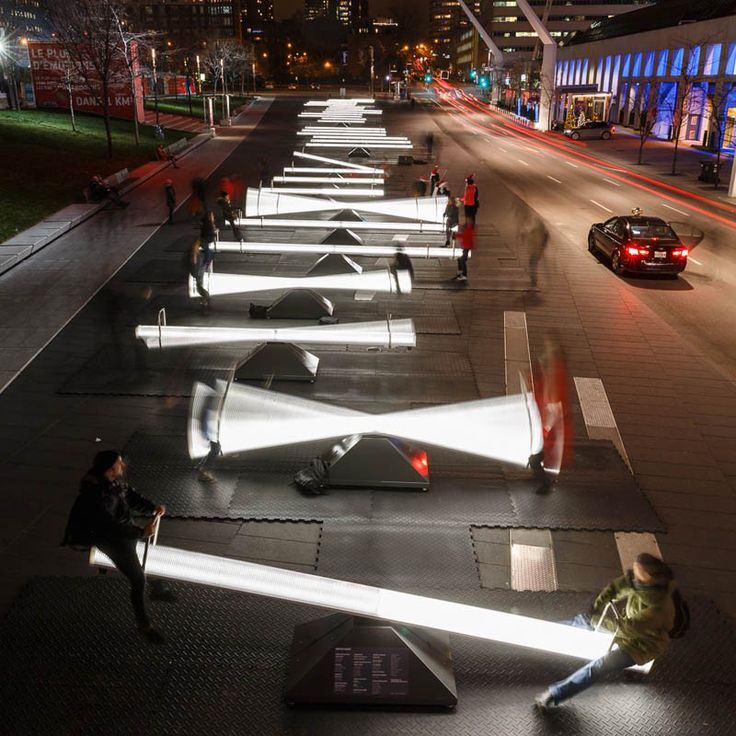 """ARTE PÚBLICA / URBANISMO - """"IMPULSE"""", esse é o mais novo projeto em exibição na Place Des Festival em Montreal, Canadá. A nova instalação é composta por 30 gangorras completamente iluminadas que emitem sons a medida que são utilizadas, resultando em diversas harmonias musicais. Há também uma série de projeções de vídeos em fachadas de edifícios próximos! O projeto faz parte de uma colaboração entre o CS Design e o Lateral Office, com sede em Toronto."""