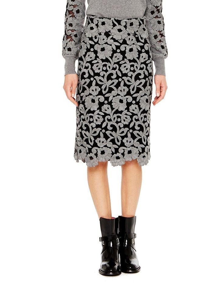 La gonna a tubino, in pizzo macramé di lana e chiusura con zip posteriore, presenta uno smerlo al fondo che segue il decoro floreale e conferisce una femminile leggerezza alla silhouette.