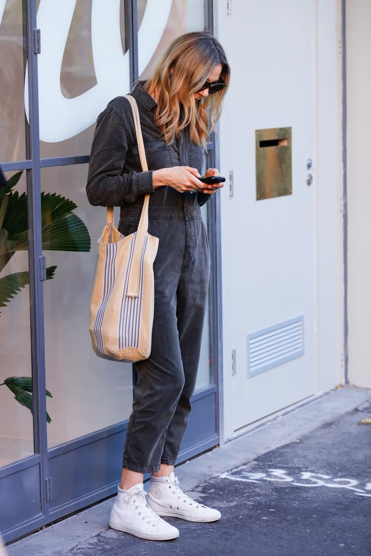 Charcoal denim jumpsuit worn with white Converse sneakers and a tote bag