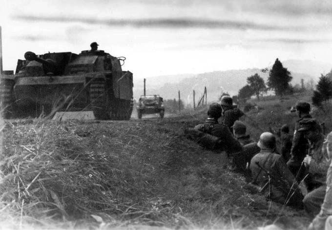 Fighting in the Carpathians, a German assault gun rolls past soldiers on the road In the background a VW Kübelwagen.