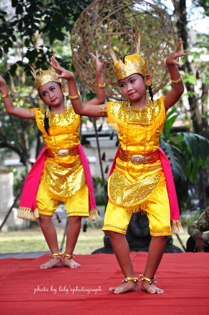Indonesian children are depicted performing in traditional performance dress.  Indonesian for