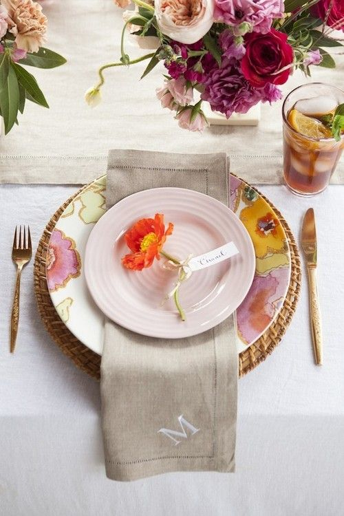 Love this colorful bloom on the salad plate with the napkin tucked between it  the dinner plate  charger