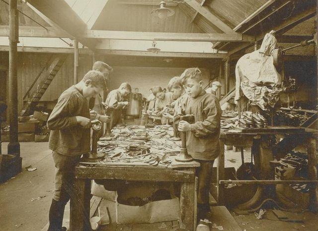 Handzwikkerij; zwikken is het op de leest vormen van de schoen; in de grote fabrieken gebeurt het voor het grootste deel machinaal; met de hand worden alleen gezwikt de mindere soorten leer en kinderschoenen; hier 14- à 15-jarige jongens in de leerschool. Schoenfabriek Jan van Arendonk, Tilburg