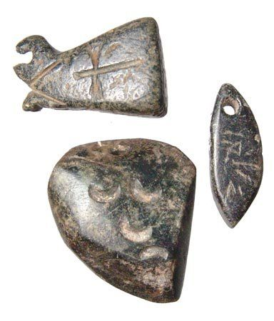 Syrian chlorite amulets, 5th-10th century A.D. Syrian chlorite amulets, first with a bird-like end with a cross on either side, the second with an Aramaic looking inscription and the last with crescents and pierced for suspension, 2.4 cm, 2.8 cm. Private collection